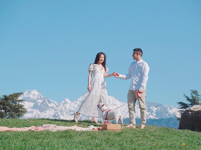 couple holding hands with mountains background